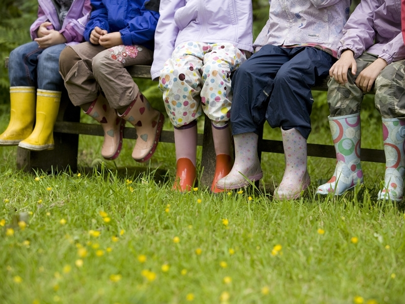 kids at the Cadbury Easter Egg Hunt. They are all sitting on a fence and they are all wearing waterproofs and wellie boots