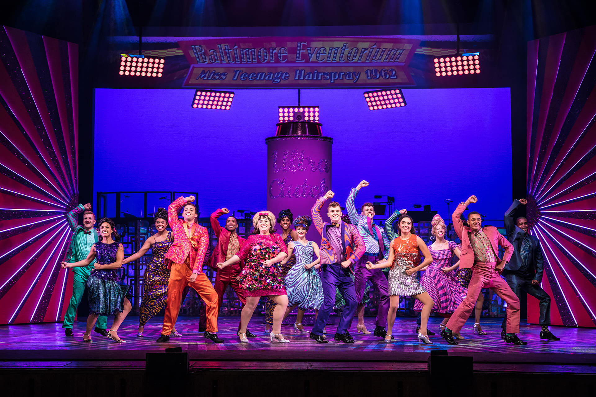 cast of Hairspray on stage dancing in sync. They are all dressed colourfully and the stage is lit up pink
