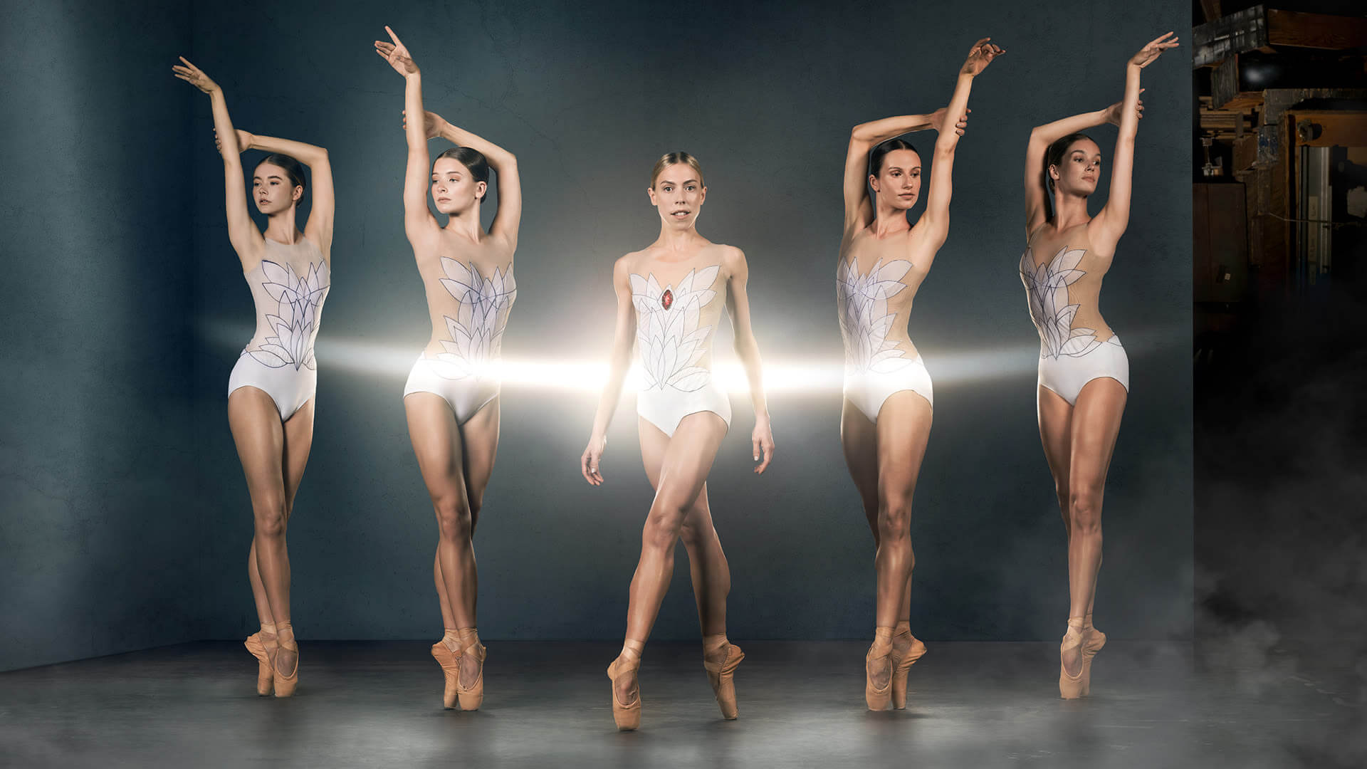 Five ballet dancers in a dance pose with the centre dancer looking to camera with a beam of light across them